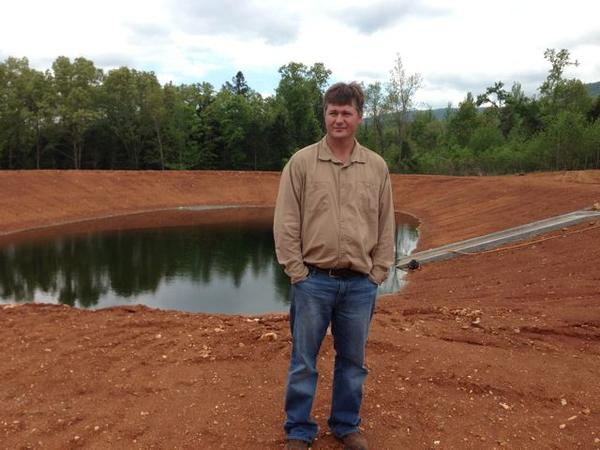 Jason Henson, owner of C&H Hog Farms, stands near one of two swine waste ponds in the spring of 2013.