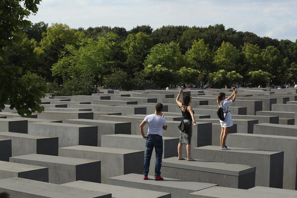 Visitors photograph each other while standing on concrete slabs at the Holocaust Memorial in Berlin in 2016.