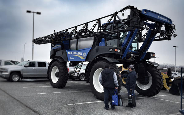 Two farmworkers admire a massive New Holland field sprayer tractor at a potato conference in Kennewick, Washington.