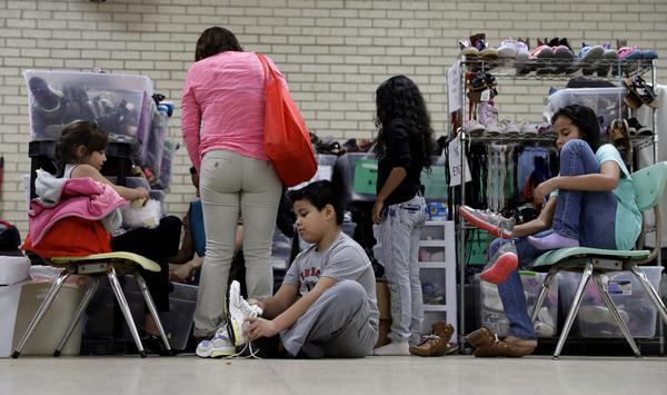 Central American migrants newly released after processing by the U.S. Customs and Border Patrol are fitted for shoes at the Sacred Heart Community Center in the Rio Grande Valley border city of McAllen, Texas, in 2016.