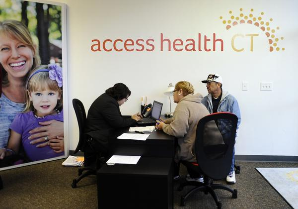 Gildred Ortiz, center and Julio Colon, right, receive help from outreach worker for Access Health CT, Cristela Solorio Ruiz during a grand opening for Connecticut's health insurance exchange's first insurance store in New Britain in 2013.