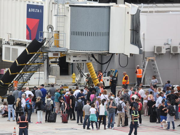 People waited on the tarmac of Fort Lauderdale-Hollywood International airport after a shooting caused Terminal 2 to be evacuated on January 6.