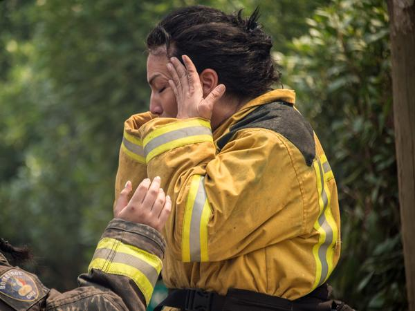A firefighter mourns the loss of a colleague during a forest fire in the coastal resort of Llico, Chile.