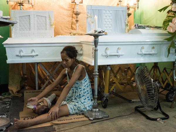 Elizabeth Manosca tends to her baby during a wake for her slain husband and 7-year-old son, who were killed when unidentified gunmen shot through the door of their home in Manila, Philippines, in December.
