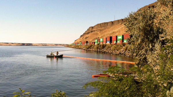 Absorbent boom is place in the Columbia River as a precaution where a BNSF locomotive leaked diesel fuel to the rail bed.