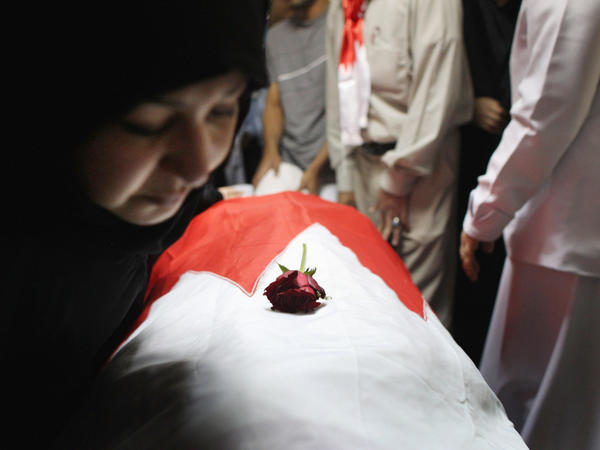 An independent commission found that the Bahrain security forces used excessive force and tortured some of those detained. Here, family members look upon the body of protester Abdul Ridha Mohammed, who was shot in the head and died of his wounds on Feb. 21, 2011.