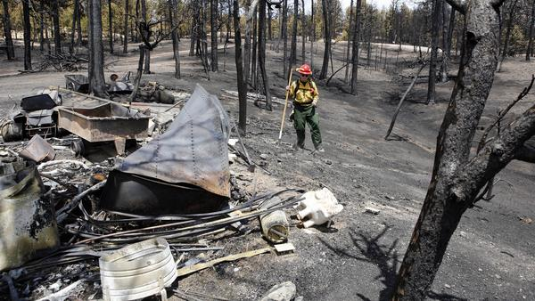 Firefighter Brandie Smith walks by the remains of a structure destroyed in the Black Forest wildfire north of Colorado Springs last month. More than 500 homes have been lost to wildfire in the state this year.