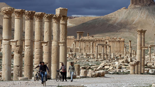 Syrian citizens ride their bicycles in Palmyra in March. Authorities in Lebanon say they have seized many looted items from Syria, including 24 statues from Palmyra.