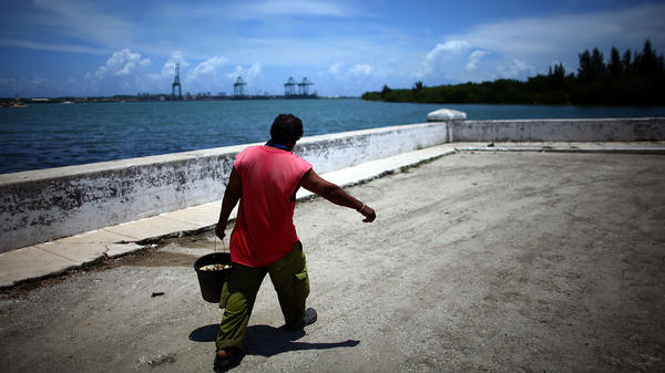 A fisherman walks the streets of Mariel, on Cuba's northwest coast. In the distance, construction is underway on the Port of Mariel, where the government is creating a special free-trade zone.