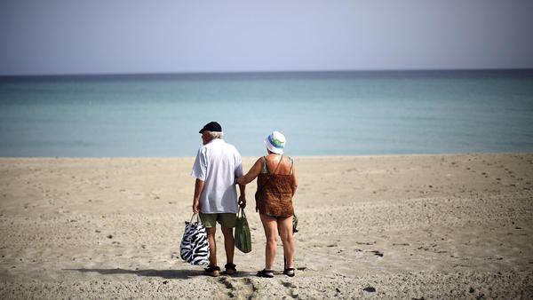 A couple walks along the beach in the resort area of Varadero, Cuba. Varadero is home to upscale hotels and resorts that cater to foreign tourists.