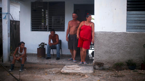The company that employs Juanito Cruz (second from right) gave his family their home. It's located near the sugar factory in Madruga, Cuba, where Cruz has worked for 31 years.