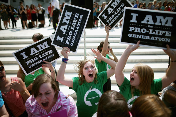 Anti-abortion advocates cheer in front of the Supreme Court on June 30 after hearing the ruling that some for-profit companies can refuse to offer contraceptive coverage on religious grounds.