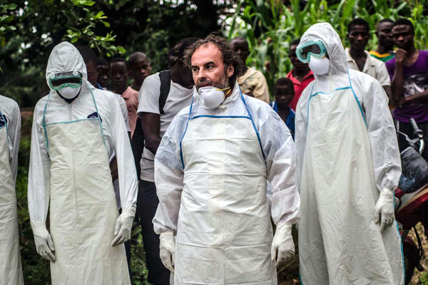 Jose Rovira (center), a World Health Organization logistics expert, trains residents of Pendembu to bury an Ebola victim without touching the body — a dramatic change in a place where family and friends traditionally wash and embrace a loved one's body.