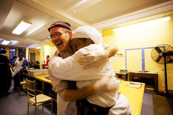 Yvonne Shields (right) hugs one of her volunteers at the Manhattan community kitchen where she works as a sous chef. A resident of Highbridge Gardens in Manhattan, Shields is also a member of the local organization Community Voices Heard.