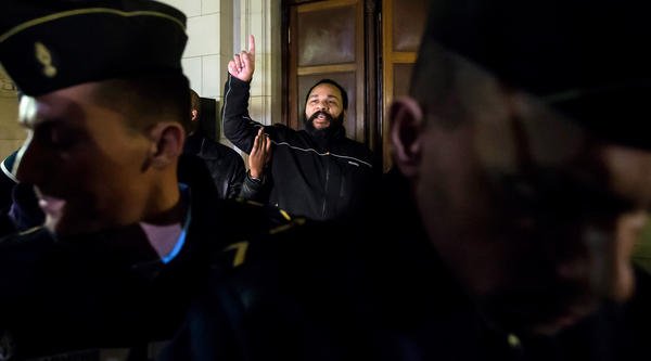 French comedian Dieudonne M'Bala M'Bala, center, gestures as he exits the courtroom after his trial in Paris last Wednesday. He was ordered to pay $37,000 for condoning terrorism. His lawyer argues he was denied the same freedom of expression that the satirical magazine <em>Charlie Hedbo </em>received.