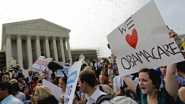 Supporters of the Affordable Care Act celebrate outside the Supreme Court in 2012, after a divided court upheld the law as constitutional by a 5-to-4 vote. The latest battle, which the Supreme Court hears Wednesday, is over whether people who buy insurance through federally run exchanges are eligible for subsidies.