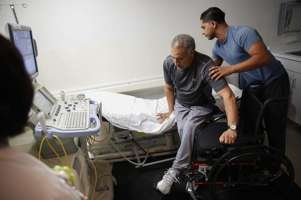 Joel Ramirez is helped onto a bed to receive an ultrasound with the aid of Francisco Guardado, his home health care giver, during a visit to the hospital in Rialto, Calif.