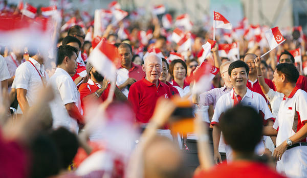 The crowd cheers as Singapore's former Prime Minister Lee Kuan Yew (center) arrives at the Marina Bay Floating Platform for the annual National Day Parade celebrations in Singapore on Aug. 9, 2012.