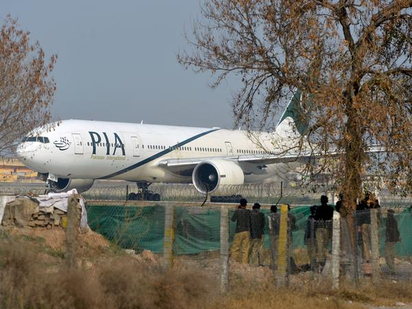 Pakistani police stand guard as a Pakistan International Airline plane taxis on a runway in Islamabad on Feb. 8. The national carrier has struggled in recent years with a $3 billion debt.