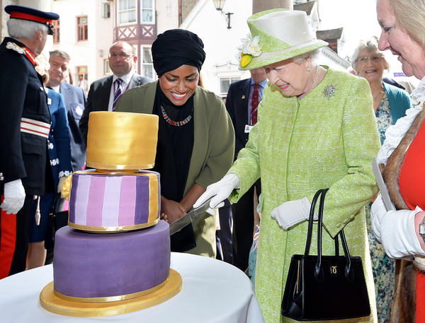 Britain's Queen Elizabeth II cuts into a birthday cake baked by Nadiya Hussain (left), winner of <em>The Great British Bake Off,</em> during celebrations of the queen's 90th birthday in Windsor, England.