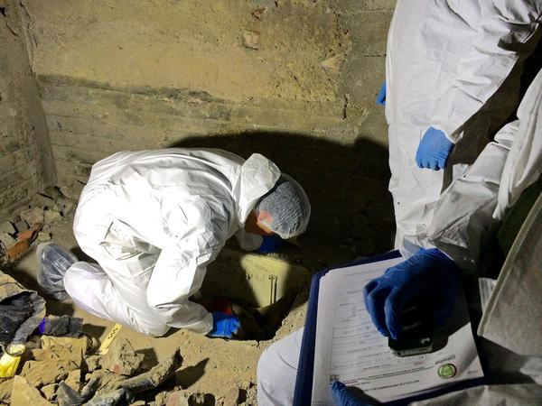 An anthropologist unearths a body at a crime scene in Chihuahua city, Mexico.