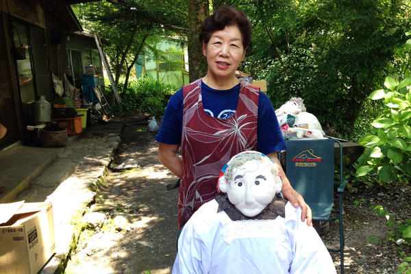 Tsukimi Ayano, 67, stands in front of her house with one of her scarecrow figures. She estimates that she's made around 400 scarecrows.