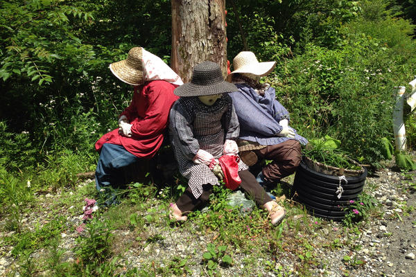 Three scarecrows lean against a telephone poll at the edge of the Japanese village Nagoro. Tsukimi Ayano created these figures after she returned to the village to take care of her father. The area now includes many of her figures and has attracted tourism.
