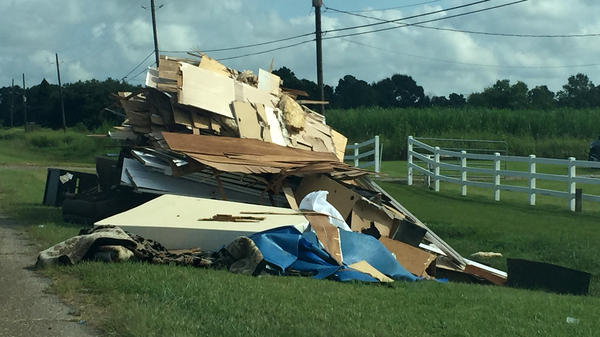 Debris from flood-damaged homes lines Highway 167 in Maurice, La.