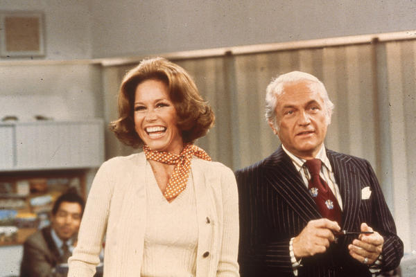 Actors Mary Tyler Moore and Ted Knight laugh in a still from <em>The Mary Tyler Moore Show</em> in 1976.