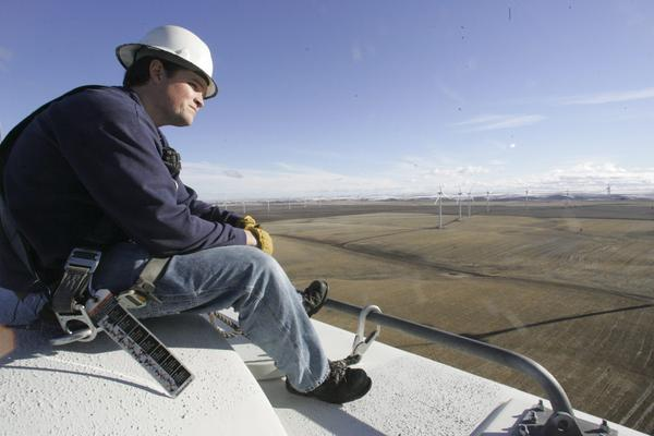 A wind plant supervisor looks over the landscape from the top of a wind turbine in January 2008 at a wind farm in Wasco, Ore. (Rick Bowmer/AP)