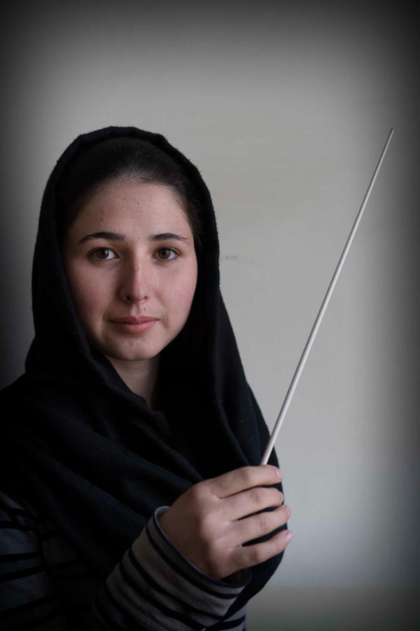 "Negin Khpolwak, who's 19, is one of the orchestra's two conductors. She has a bit of stage fright when she steps into the spotlight. Then, she says, ""I see the smile on the girls' faces when they play, and I don't think about anything else."""