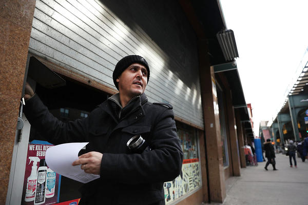 A Yemeni business owner closes the gate to his store Thursday in the Brooklyn borough of New York City. Across the city, Yemeni-owned bodega and grocery stores will shut down from noon to 8 p.m. to protest President Trump's executive order banning immigrants and refugees from seven Muslim-majority countries, including Yemen.
