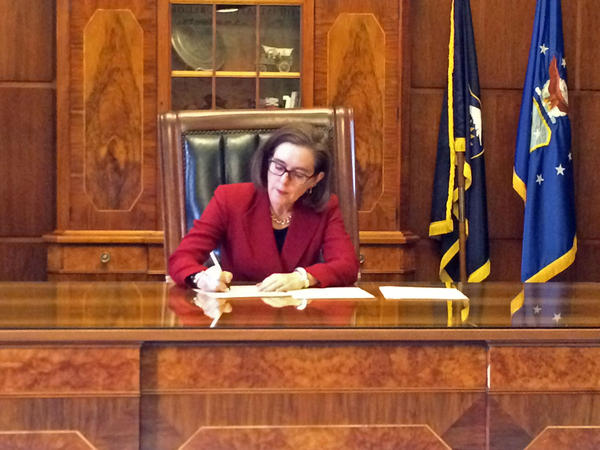 Oregon Gov. Kate Brown signs an executive order on immigration policies at the State Capitol in Salem.