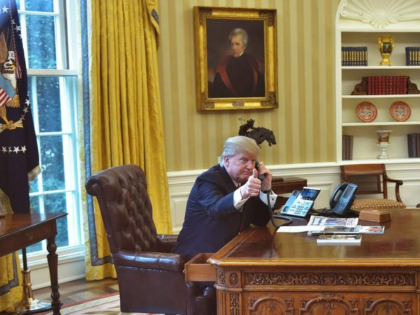 President Trump gives a thumbs up as he speaks on the phone in the Oval Office on Jan. 29.