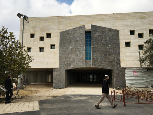 A settler walks past a new building in Beit El's yeshiva complex. Trump's pick for ambassador, David Friedman, has raised money for the yeshivas in Beit El.