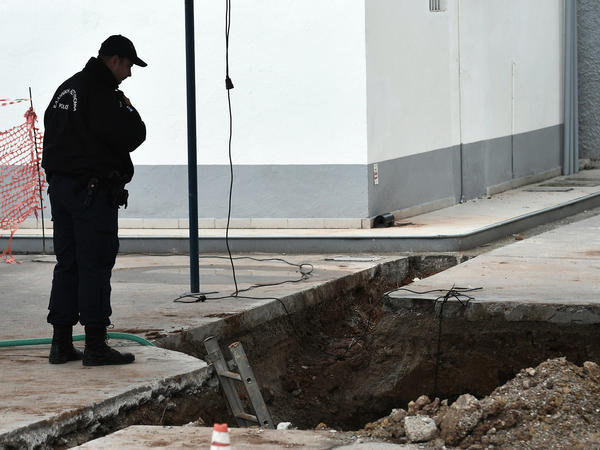On Wednesday, a police officer looks into the hole where an unexploded World War II-era bomb was found during work on a gas station's underground tanks. The city plans a massive evacuation Sunday to defuse and remove the bomb.