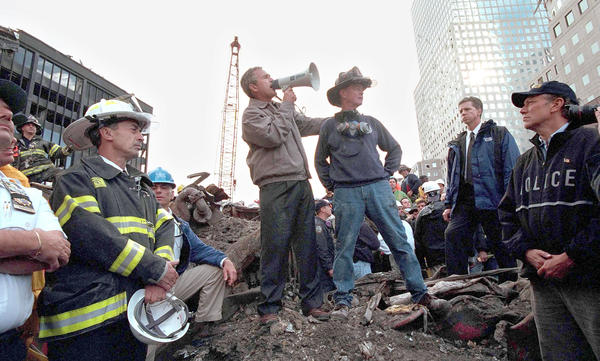 President George W. Bush speaks to rescue workers from the rubble of Ground Zero on Sept. 14, 2001 in New York City. Bush's moves for tougher immigration measures won widespread support then, compared to the resistance President Trump is facing today.