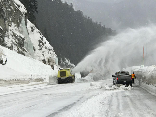 A snow blower sends snow flying through the air during clearing efforts of US-2 Stevens Pass on Friday. The pass opened to traffic shortly after 12 p.m..