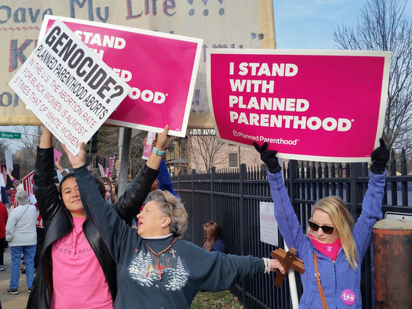 Planned Parenthood supporters and an opponent of the organization try to block each other's signs during a protest and counterprotest Saturday in St. Louis.
