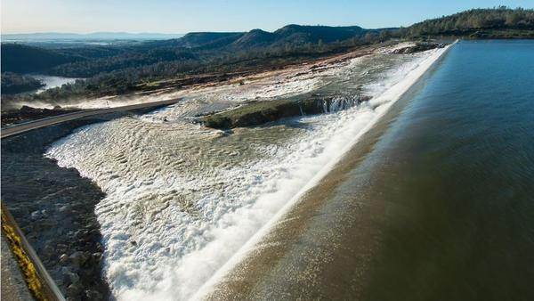 In this scene from Saturday, water is seen flowing over the auxiliary spillway at Oroville Dam, after the lake level exceeded 901 feet above sea level. The water carved a path to the Feather River, in the distance.