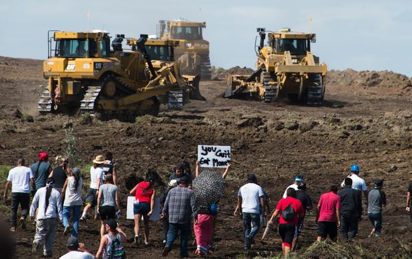 Native American protesters and their supporters approach construction crews during a demonstration against work being done for the Dakota Access Pipeline near Cannon Ball, N.D., on Sept. 3, 2016.