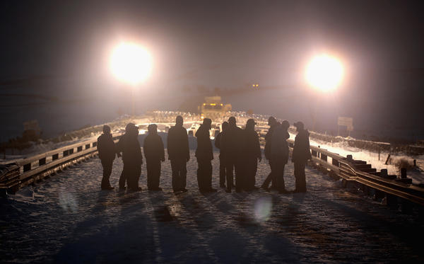 Military veterans protesting the pipeline stand opposite police guarding a bridge at the edge of the Standing Rock Sioux Reservation on Dec. 1, 2016.