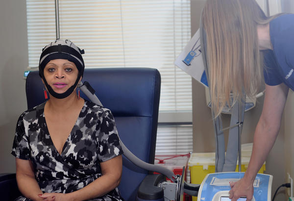 Claudette Foreman, a research coordinator at Baylor College of Medicine, demonstrates the Paxman cooling device. Some women reported chills, headaches and nausea when using the device.