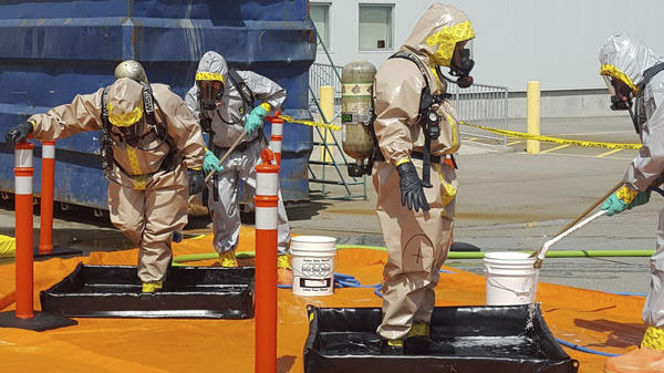 Members of the Royal Canadian Mounted Police go through a decontamination procedure after intercepting a package containing around 1 kilogram (2.2 pounds) of the powerful opioid carfentanil, imported from China to Vancouver. China has now added the drug to its list of controlled substances.