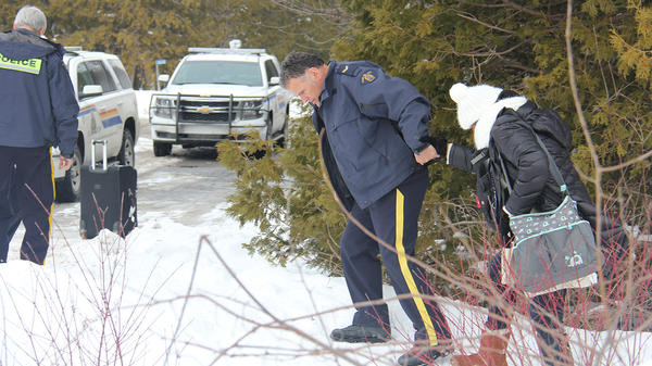 A Canadian police officer offers a hand to a migrant crossing the U.S.-Canada border near Champlain, N.Y., on Wednesday. The Royal Canadian Mounted Police are reporting surges in illegal crossings in Canada in recent months.