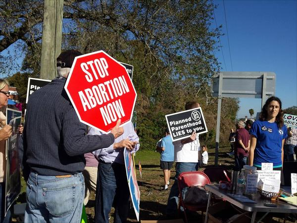 Protestors hold anti-abortion signs in front of a Temple Terrace Planned Parenthood Saturday
