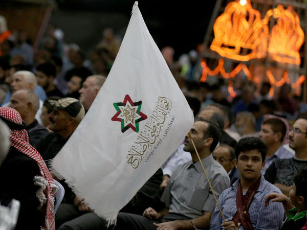 """Supporters attend a gathering for Jordan's National Alliance for Reform, a political bloc including the Muslim Brotherhood, in Amman's Sweileh District last September. """"In a lot of countries, we are in partnership with governments and parliament,"""" says a brotherhood spokesman in Amman."""