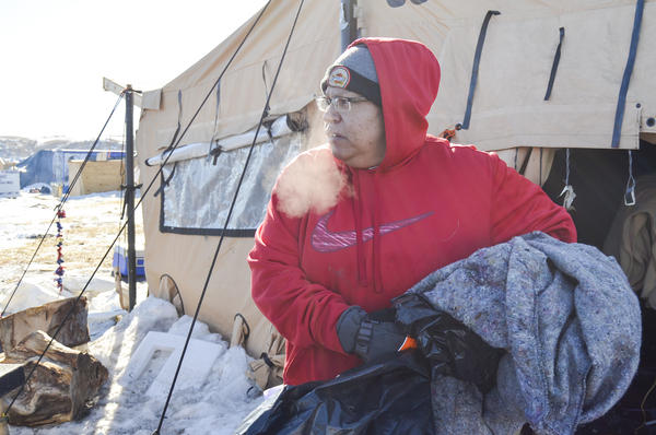 Dotty Agard of the Standing Rock Sioux tribe sorts through abandoned goods at camp. Tribal members and several hundred protesters are assisting with the cleanup.