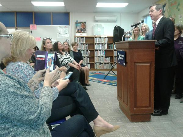 Gov. Roy Cooper announced pay increases for teachers at Collinswood Language Academy in Charlotte, as teachers look on