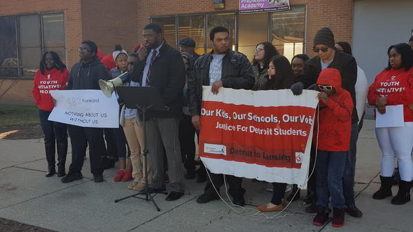 Parents, students and community activists holding signs at a press conference in front of Osborn High School in Detroit.